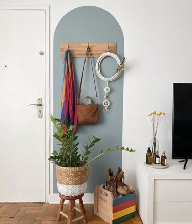 Entryway with sky blue arch accent, wood coat rack and a woven basket.