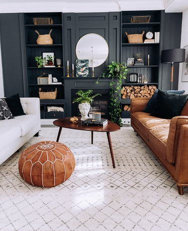 Sophisticated living room with dark gray built in bookcases and camel leather couch.