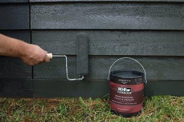 Rolling dark gray paint onto cedar shed