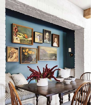 Kitchen nook with wood table, bright white brick and blue green paint behind a gallery wall.