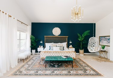 Bright bedroom with dark blue accent wall, white curtains and a boho hanging chair.
