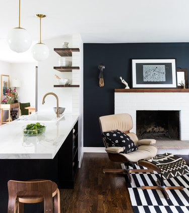 Living room with black accent wall, white fireplace and graphic line rug.