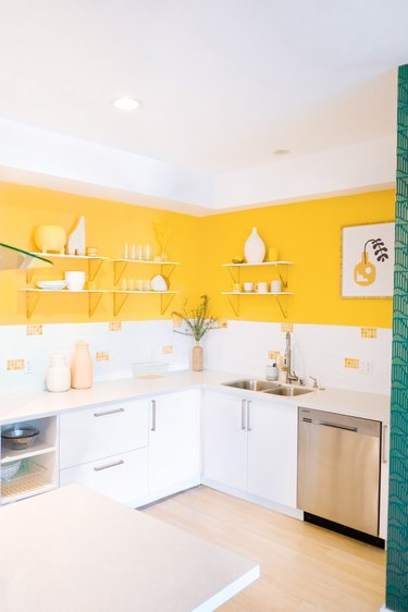Bright kitchen with yellow wall paint and white cabinets.