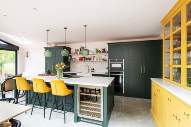 Kitchen with dark green cabinets and yellow barstools.