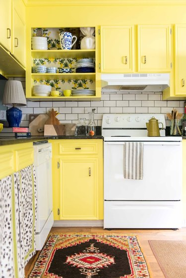 Bright yellow kitchen cabinets with white subway tile backsplash.