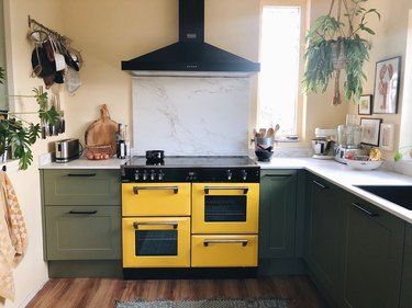 Bohemian kitchen with a yellow stove, green cabinets and hanging pots.