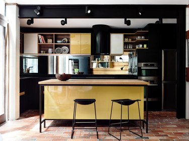 Dark kitchen with black wall paint and yellow cabinets.