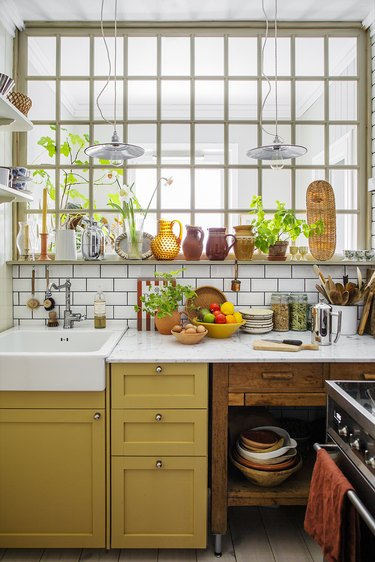 Eclectic kitchen with mustard yellow lower cabinets, a farmhouse sink and green plants.
