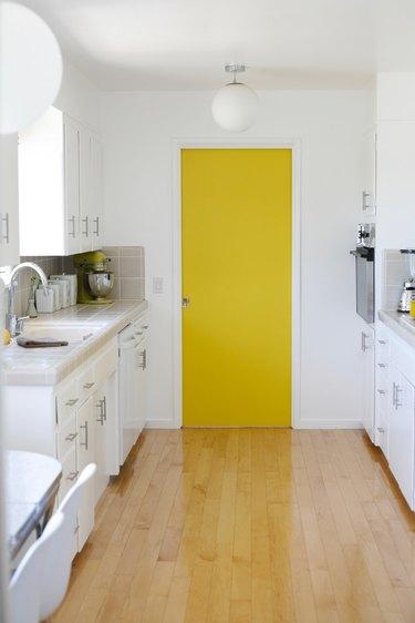 White minimalist kitchen with bright yellow pantry door.