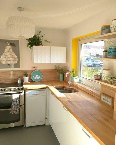 White minimalist kitchen with butcher block countertops and yellow window trim.