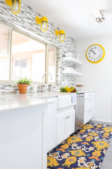 White kitchen with grey and white backsplash, a farmhouse sink and yellow industrial light fixtures.