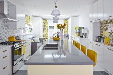 Grey and yellow kitchen with pendant lights and patterned backsplash.