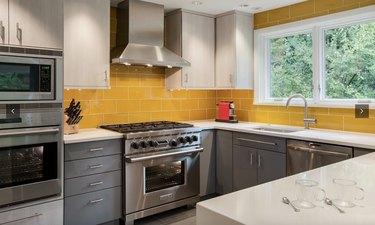 Kitchen with dark grey cabinets and yellow subway tile backsplash.