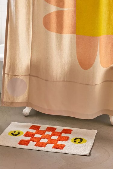 shower curtain with flower near bath mat with checkers and smiley faces