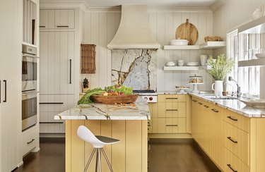 Rustic kitchen with yellow wood panel cabinets, marble countertops and open shelving.