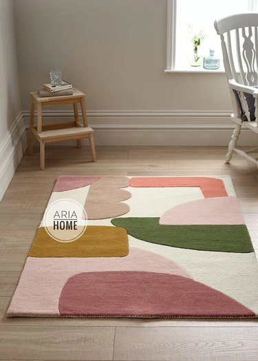 area with tufted rug in abstract pattern