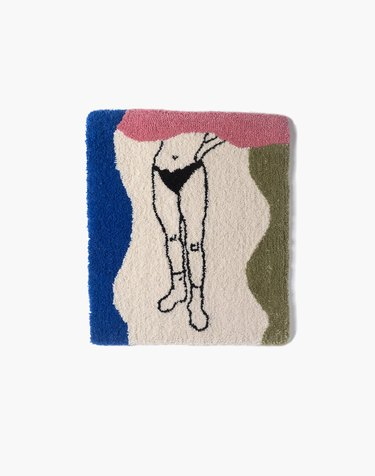 tufted rug with multiple colors and outline of the bottom half of a person's body