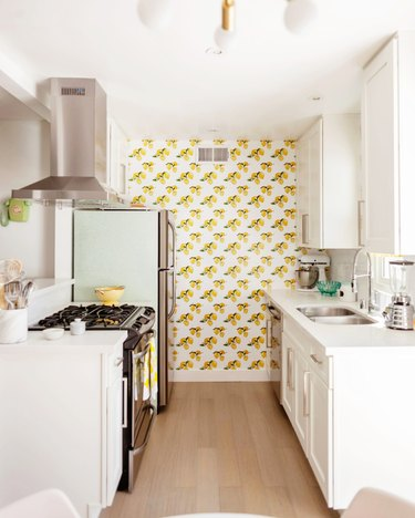 Small kitchen with white cabinets and lemon patterned wallpaper.