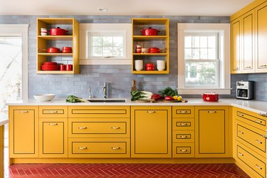 Bold kitchen with yellow cabinets, open shelving, red herringbone floor tiles and cool blue tile backsplash.