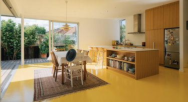 Bold kitchen with light wood cabinets and yellow floors.