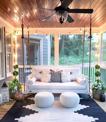 covered porch with string lights and hanging sofa