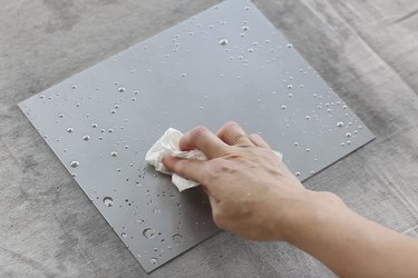 Blotting droplets of vinegar from painted glass with paper towel