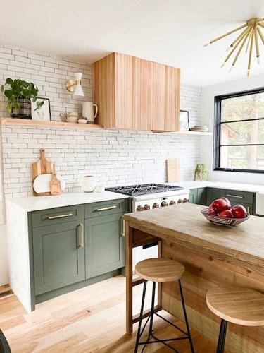 white subway tile backsplash in modern kitchen with green cabinets
