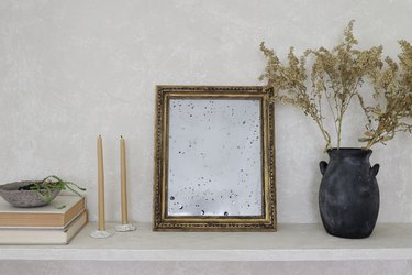 DIY antique gold mirror on shelf with dried flowers and beeswax candles