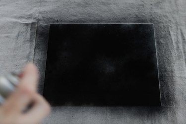 Spraying glass with black spray paint