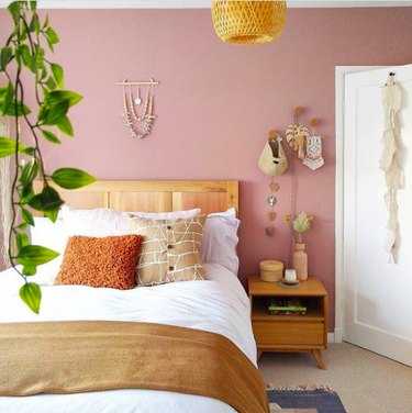 Boho bedroom with hanging plants, macrame accents and mauve wall paint.