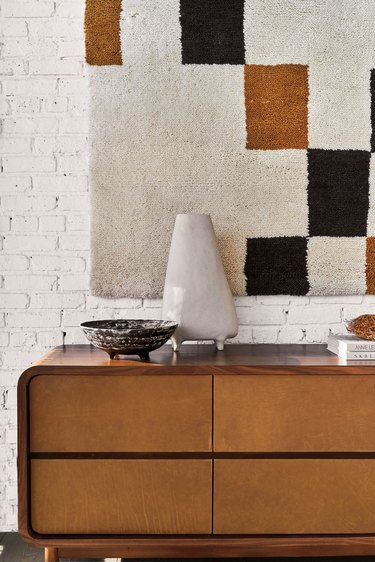 wood dresser in front of white brick wall with geometric wall hanging