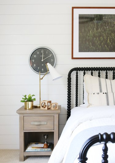 bedroom with antique bed frame and shiplap wall