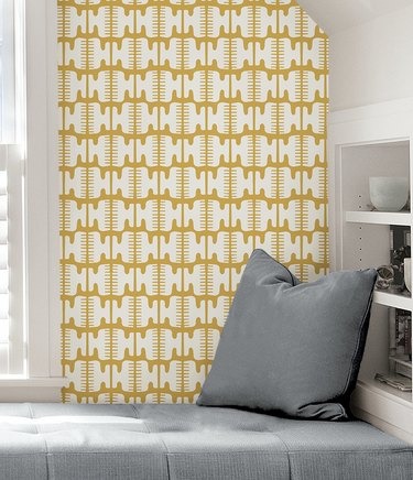 ochre-and-white patterned wallpaper near gray seating area and gray pillow