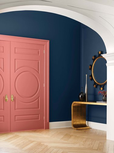 entryway with navy walls and coral door