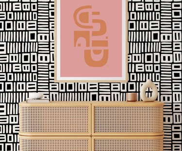 wood console in front of black and white geometric print wallpaper