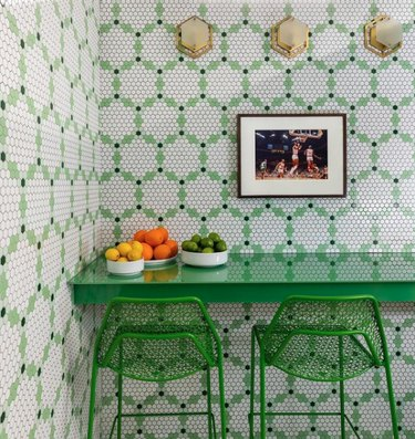 Green and white tiled kitchen with green chairs