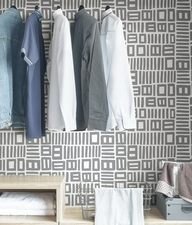 closet with blue and white shirts hanging in front of a gray-and-white patterned wallpaper