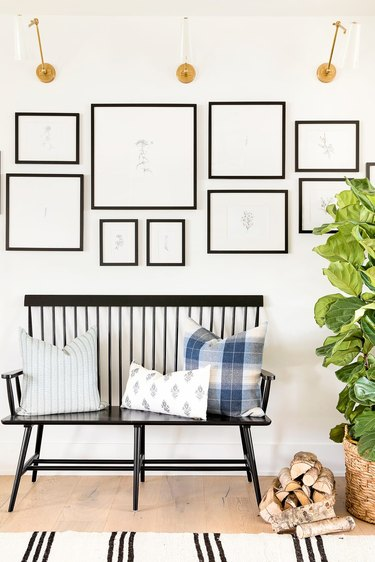 black and white gallery wall with brass sconces and bench