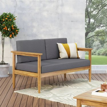 Outdoor loveseat with grey cushions and acacia wood