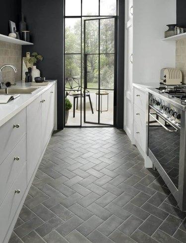 moody scandinavian kitchen with dark floor tiles