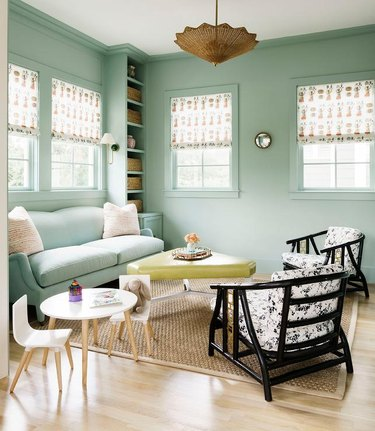 mint green living room with black chairs and pear green ottoman