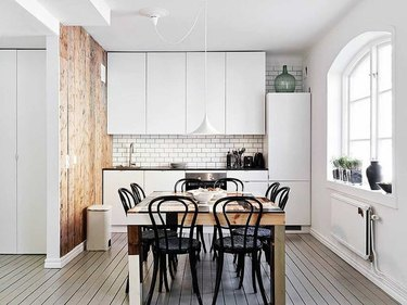 white scandinavian kitchen with subway tile and wooden dining table in the middle