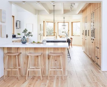 white scandinavian kitchen with wooden floors and cabinets