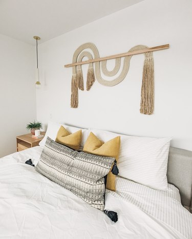 minimalist white bedroom with woven wall hanging
