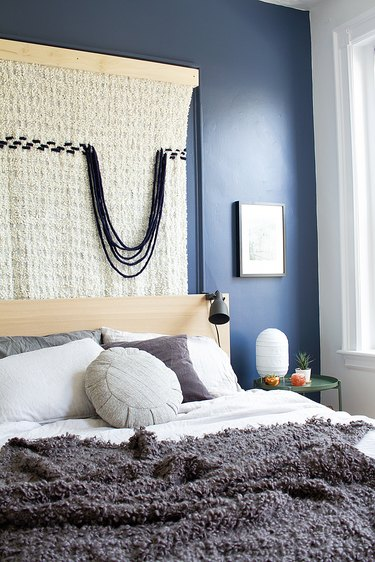 fabric wall hanging in bedroom with blue accent wall