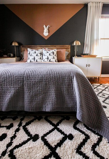 black and rust bedroom with geometric mural