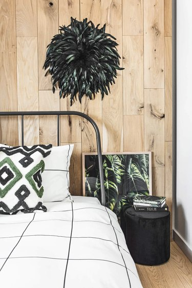 feather juju hat against wood paneling in bedroom