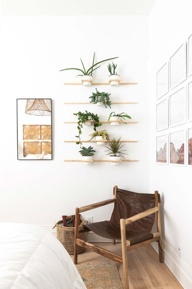 boho bedroom with wall of potted plants and chair
