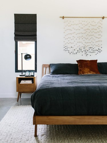 beaded wall hanging above bed with black comforter