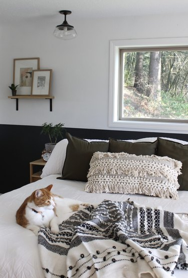 boho bedroom with floating shelf and leaning artwork
